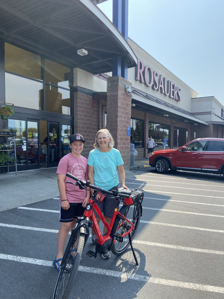 Sue Lake and her grandson standing with her new E-Bike